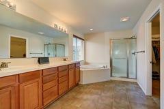 Trevligt badrum med massor av utrymme Moderna bruna kabinetter, den dubbla vasken och det vita badet för hörn badar Arkivfoto