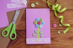 Trevligt hälsningkort som göras av en unge för moderdagen, faderdag, mars 8, födelsedag Handgjort kort med en blomma från träknap Royaltyfri Bild