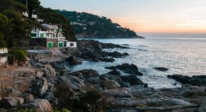 Trevligt kust- hus på soluppgång arkivbild