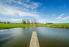 Trevligt privat damm med bron i trevlig solig dag Royaltyfria Bilder