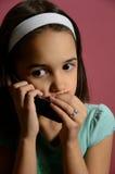 Träffande hemligheter för liten flicka på telefonen Fotografering för Bildbyråer