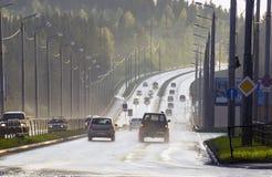 Tráfico auto después de la lluvia en el tiempo de la puesta del sol Fotos de archivo