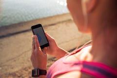 Trägt die Frau zur Schau, die intelligentes Telefon verwendet Stockfotografie