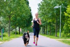 Trägt im Freien - die junge Frau zur Schau, die mit Hund im Park läuft Lizenzfreie Stockfotos