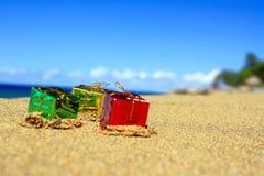 Trhee Farben-Geschenkkästen auf Strand von Ozean Stockbilder