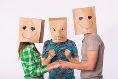 Triángulo de amor, celos y concepto del amor no correspondido - mujer y hombre con los bolsos sobre las cabezas que detienen las  Foto de archivo