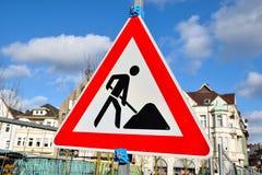 Triángulo de la señal de tráfico de las obras en fase de creación aislado en fondo nublado Fotografía de archivo libre de regalías