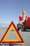 Triângulo de advertência com a mulher na chamada pelo carro na estrada Imagem de Stock