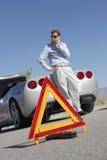 Triângulo de advertência com o homem na chamada pelo carro na estrada Imagem de Stock