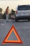 Triângulo de advertência com pares e carro no fundo imagem de stock royalty free