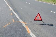 Triângulo de advertência na estrada após o acidente de viação Fotografia de Stock