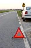 Triângulo de advertência na estrada reta imagem de stock
