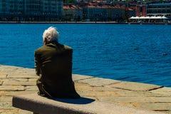 Triëst, Italië - 29 April 2017: Een oude mens op Molo Audace Stock Foto