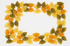 Tri Color Bow Tie Pasta Border on White Background Stock Photos