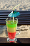 Tri-color cocktail straws on the background of sand and sun loungers, a sunny beach Royalty Free Stock Images