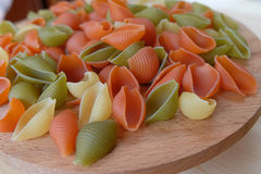 Tri-color pasta shells on the wood. Images contains of tri-color pasta shells on the wood Stock Photography