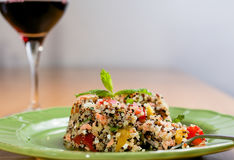 Tri-color quinoa cooked. Closeup on green plate with tri-color quinoa salad on wooden table, with a glass of wine in the background - quinoa is a pseudograin Stock Photography