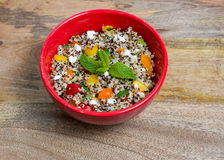 Tri-color quinoa cooked. Closeup on red bowl with tri-color quinoa salad on wooden background - quinoa is a pseudograin that has all nine essential amino-acids Stock Photography