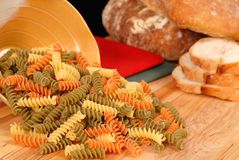 Tri-colored fusilli pasta. Uncooked tri-colored fusilli pasta spilling out of bowl onto cutting board with italian bread Royalty Free Stock Photo
