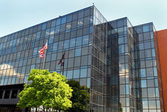 Tri-level Glass Building. Tri-level glass business building with American flag Royalty Free Stock Photo