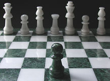 The trial. A black marble pawn metaphorically in front of judges of the white pieces Royalty Free Stock Photos