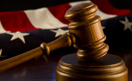 Trial in America. A judge's gavel in the foreground with an American flag in the background Stock Image