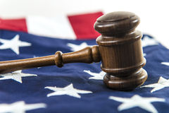 Trial in America. A judge's gavel in the foreground with an American flag in the background Stock Images