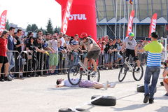 Trial biker jumping over lying man. A trial biker jumping over a lying man at the Iubim 2 roti (We love two wheels) event in Romania, at Romexpo. At this event Royalty Free Stock Images