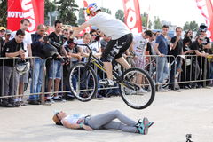 Trial biker jumping over woman. A trial biker jumping over a woman at the Iubim 2 roti event in Romania, at Romexpo. At this event it was seen a show made of Royalty Free Stock Photography