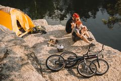 trial bikers resting near tent and cycles on rocky cliff stock photography