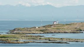 Trial Islands, Victoria 4K UHD. The lighthouse on the Trial Islands, near Victoria on Vancouver Island. The Olympic Mountain range, in Washington State, is in stock footage