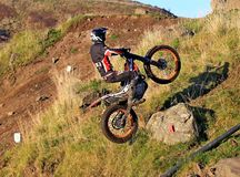 Trial motorcyclist standing on bike wheelie Stock Images
