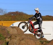 Trial motorcyclist standing on rocks Stock Images