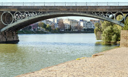 Triana bridge. Located in the Spanish city of Seville, across the river Guadalquivir in the background are the houses of the popular neighborhood of Seville Stock Photos