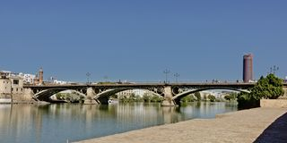 Triana bridge over Guadalquivir river in Seville, Spain. Triana or Isabel II historical arch bridge over Guadalquivir river in Seville,  Spain, with modern royalty free stock photo