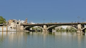 Triana bridge over Guadalquivir river in Seville, Spain. Triana or Isabel II historical arch bridge over Guadalquivir river in Seville, Spain royalty free stock photos