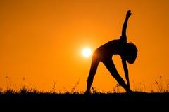 Triangeln poserar yoga med den silhouetted unga kvinnan Arkivbilder