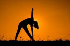 Triangeln poserar yoga med den silhouetted unga kvinnan Arkivfoton