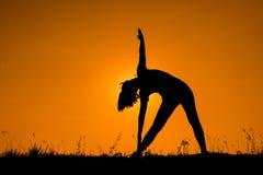 Triangeln poserar yoga med den silhouetted unga kvinnan Royaltyfri Foto