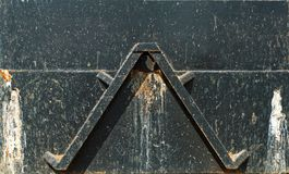 Triangle on black plate. Iron triangle on a black plate with traces of rust an dirt Royalty Free Stock Photography