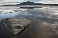 Triangle Boulder On Reflective Lake Stock Photo