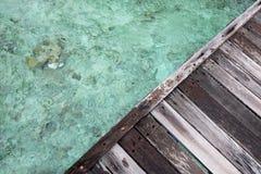 Triangle en bois de dock au-dessus de l'eau claire images stock