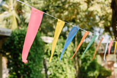 Triangle flags hanging on the rope against the blue sky and tree. With natural lighting. Multi colored triangular flags on celebration party Stock Image