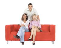 Triangle Of Friends. Two smiling women sitting on an orange couch, and a smiling man standing in the middle behind them.  Isolated on white background, in studio Stock Photos