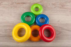 Triangle made of color plastic toy rings lay on table Stock Photography