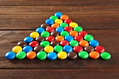Triangle made of colorful candies. On wooden background stock images