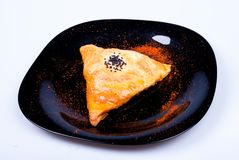 Triangle with meat. Pastries with meat covered with seeds and paprika Stock Images