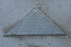 Triangle on a metal tearplate. Grey metal tear plate with triangle form, pattern and structure Royalty Free Stock Photos