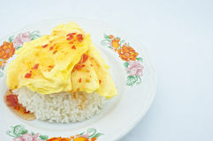 Triangle omelette on rice. Omelette made a triangle put on rice placed on the plate with white background Royalty Free Stock Image