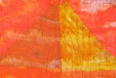 Triangle pattern on stitched orange silk batik Stock Image